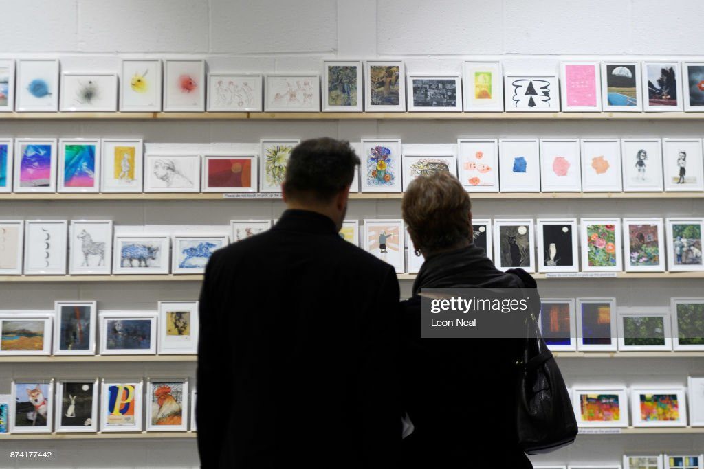 A couple look at some of the anonymously decorated postcards as they are displayed at a preview for the 'Art on a Postcard' event ahead of the upcoming secret auction, on November 14, 2017 in London, England. The auction will take place on 16 November and will raise money for the Hepatitis C Trust. Artists who have contributed work include Peter Blake and Bob & Roberta Smith.
