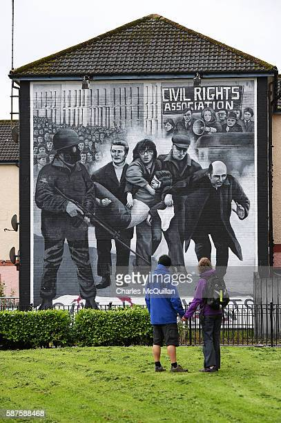 A couple look at the mural on Free Derry Corner depicting an image of Bishop Daly as parishioners and well wishers pay their respects to the late...