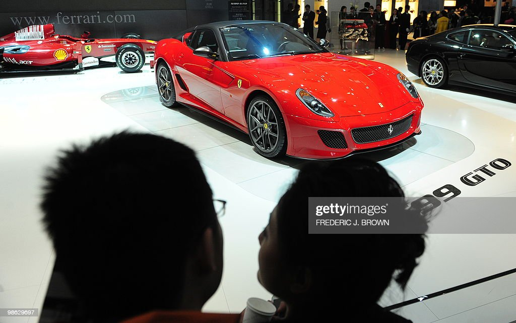A couple look at the newly launched Ferrari 599 GTO, the Italian carmaker's fastest road car yet with a top speed of 335 kilometres (208 miles) an hour, during a media preview at the Beiijng Auto Show on April 23, 2010. Auto sales in booming China hit 13.64 million in 2009, overtaking the US, as increasingly well-off Chinese consumers continued to snap up cars, helped by government incentives such as lower taxes. AFP PHOTO/Frederic J. BROWN