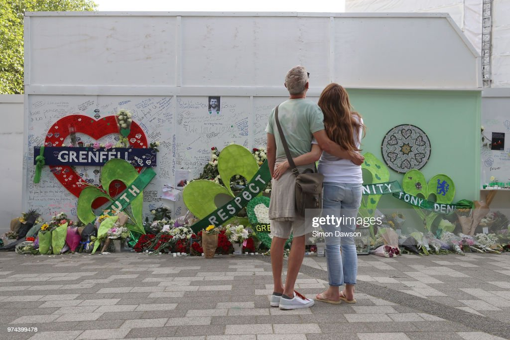 A couple look at tributes left at a memorial wall by Grenfell Tower on the one year anniversary of the Grenfell Tower fire on June 14, 2018 in London, England. In one of Britain's worst urban tragedies since World War II, a devastating fire broke out in the 24-storey Grenfell Tower on June 14, 2017 where 72 people died from the blaze in the public housing building of North Kensington area of London.
