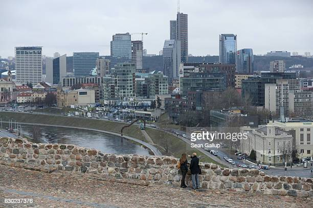 A couple look out at the city's business district from the hill of Gediminas Castle on November 25 2016 in Vilnius Lithuania Vilnius is the capital...