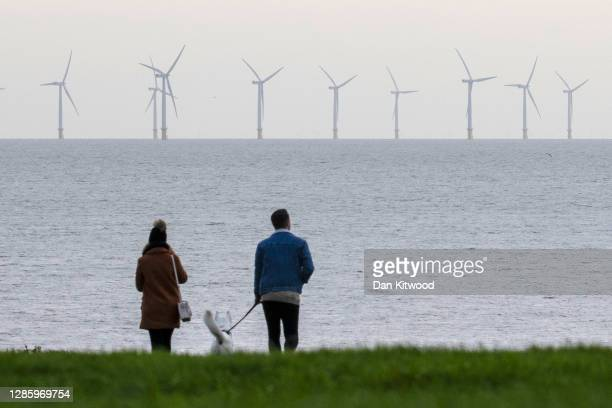 A couple look out at wind turbines off the coast of Essex on November 16 2020 in FrintononSea England Wind energy features prominently in Prime...