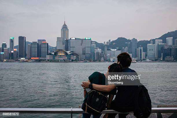 A couple look out from the waterfront in the Tsim Sha Tsui district as buildings across the Victoria Harbour stand in Hong Kong China on Tuesday Aug...