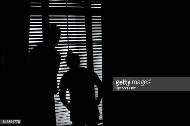 A couple look out the window as they wait out Hurricane Irma in a hotel on September 9 2017 in Fort Myers Florida With businesses closed thousands in...