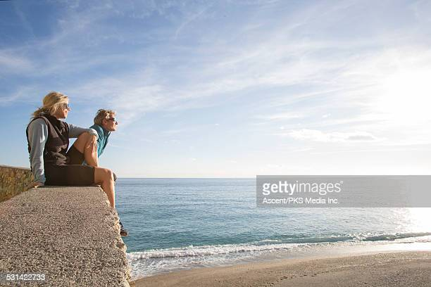 Couple look out to sea from stone wall perch