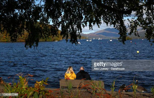 Couple look out towards Lake Windermere from Bowness-on-Windermere on October 10, 2020 in Windermere, England.