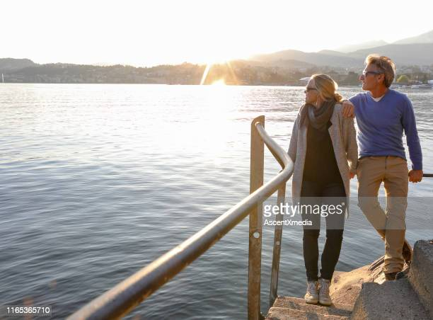 couple look over lake at sunrise from lakeside walkway - ricchezza foto e immagini stock