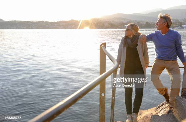 couple look over lake at sunrise from lakeside walkway - switzerland stock pictures, royalty-free photos & images