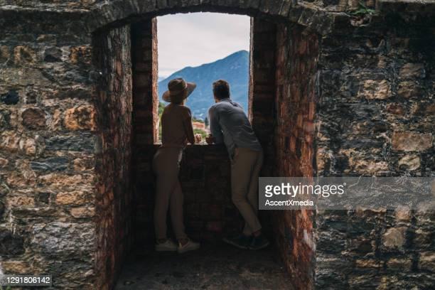 couple look through window in ancient italian village - look back at early colour photography imagens e fotografias de stock