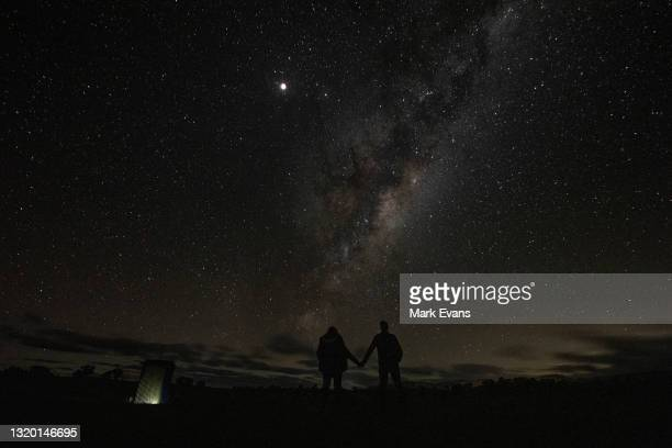 Couple look towards the supermoon and the milky way on May 26, 2021 in Rylstone, Australia. It is the first total lunar eclipse in more than two...