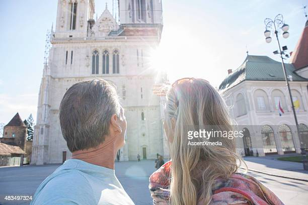 Couple look up towards cathedral in sunlight