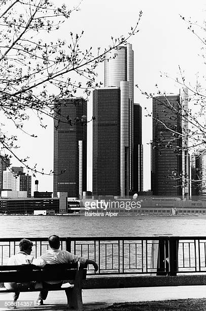 A couple looking across the Detroit River from Windsor Ontario Canada towards the Renaissance Center on the International Riverfront in Detroit...
