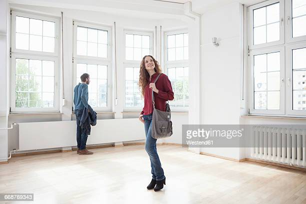 Couple looking around in empty apartment