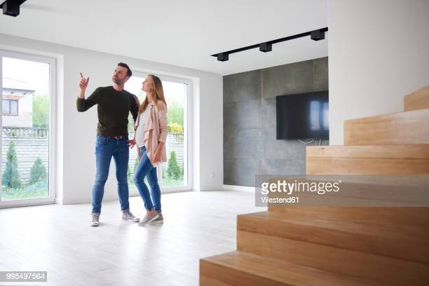 couple looking around in empty flat - casal heterossexual imagens e fotografias de stock