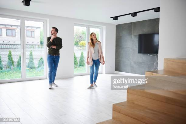couple looking around in empty flat - couples nus photos et images de collection