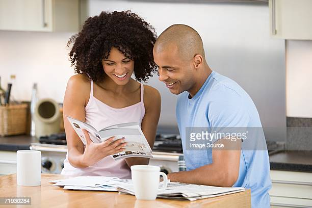 Couple looking at a brochure in kitchen