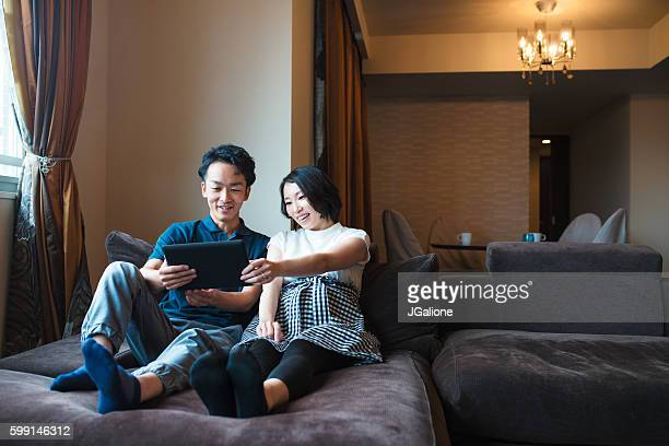 couple looking at a digital tablet together - redoubtable film stock photos and pictures