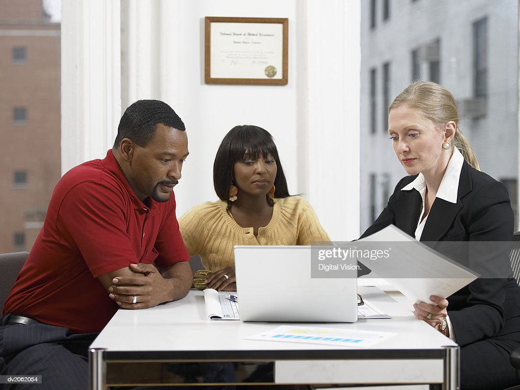 Couple Looking at a Doctor's Laptop in Her Clinic : Stock Photo
