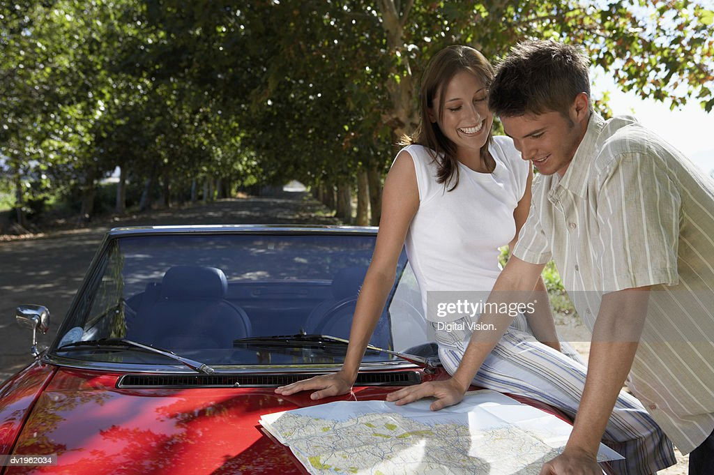 Couple Looking at a Map on a Convertible Car Bonnet : Stock Photo