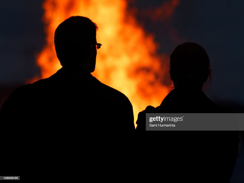 A couple looking at a midsummer bonfire : Stock Photo