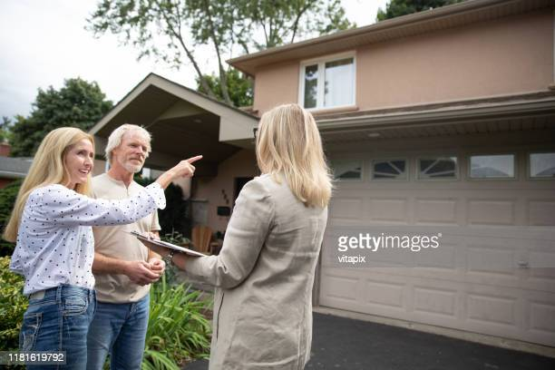 couple looking at a new house - examining stock pictures, royalty-free photos & images