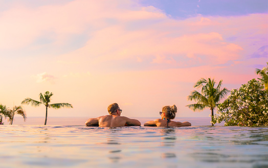 Couple looking at beautiful sunset in infinity pool 889473622