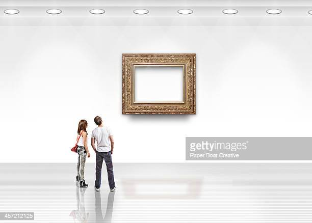 couple looking at blank art with gold frame - art gallery stock pictures, royalty-free photos & images