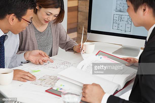 couple looking at blueprint of their new house at office - real estate office stock photos and pictures