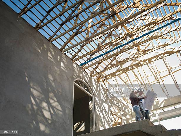 couple looking at blueprints in house under construction - reform stock pictures, royalty-free photos & images