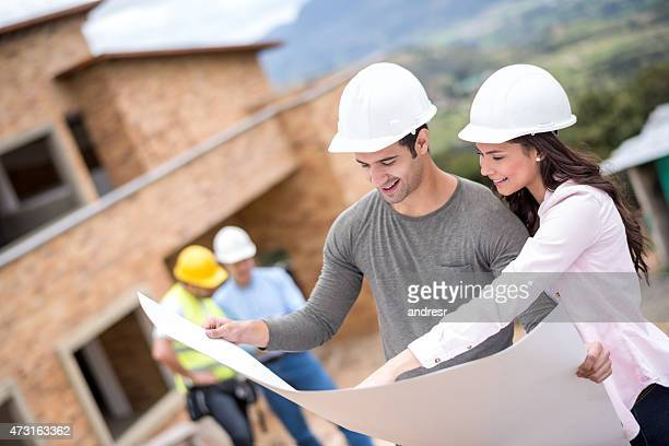 Couple looking at blueprints of a house