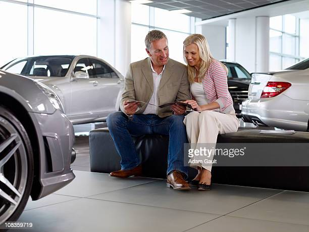Couple looking at brochure in automobile showroom