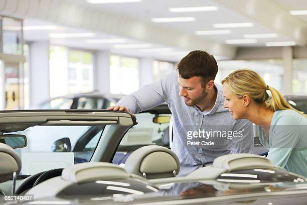 Couple looking at car for sale in showroom