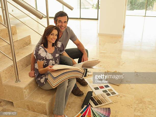 Couple looking at carpet samples in empty house