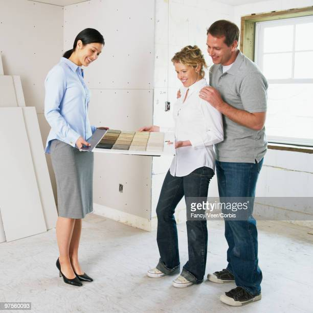 Couple looking at carpet samples with interior designer