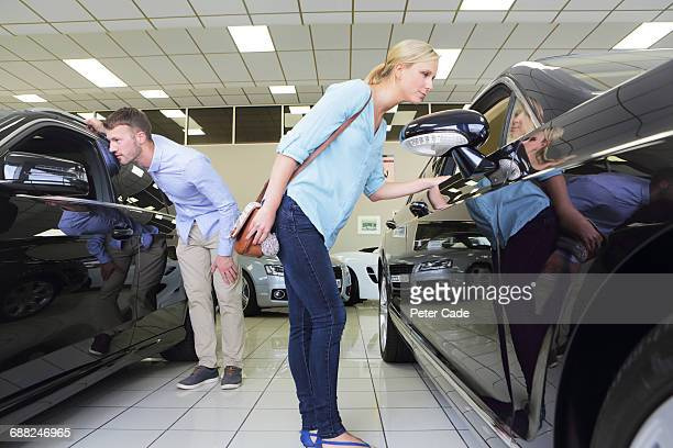 Couple looking at cars in showroom