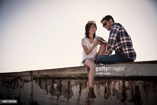 Couple looking at cell phone on cement wall