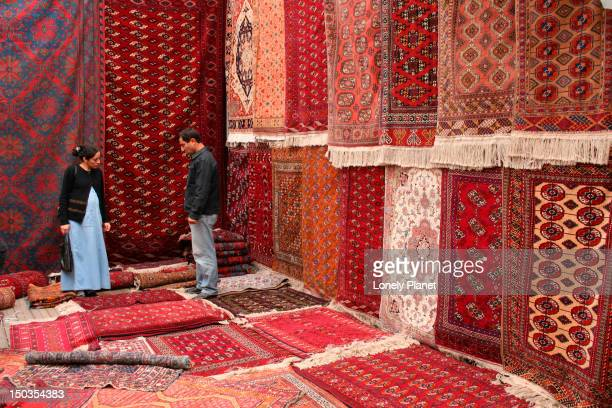 Couple looking at Central Asian carpets for sale at Vernisazh  Market.