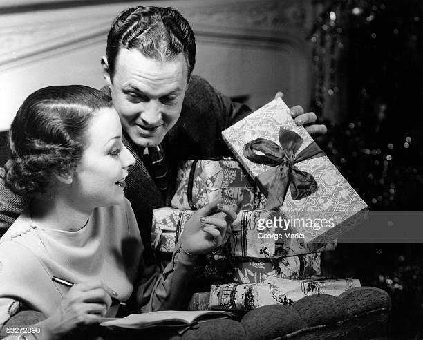 couple looking at christmas gifts - noel noir et blanc photos et images de collection