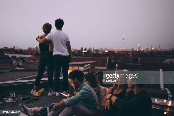 couple looking at city while friends relaxing on terrace during rooftop party - aussicht genießen stock-fotos und bilder