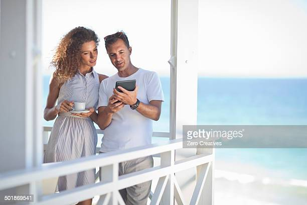 Couple looking at digital tablet on beach house balcony