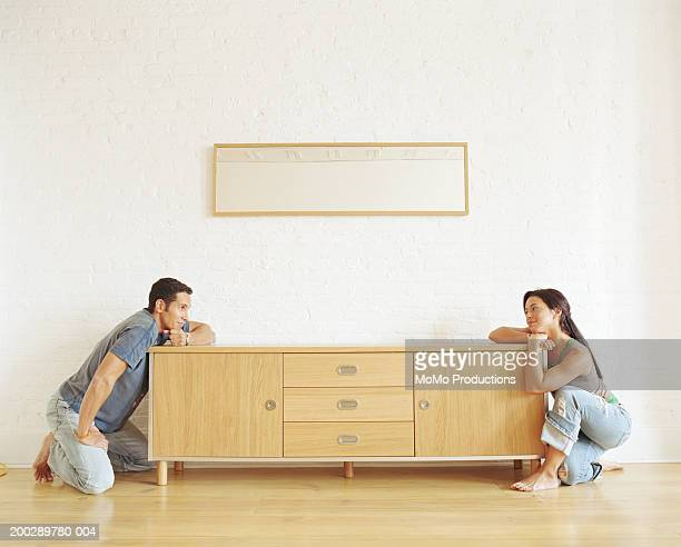 couple looking at each other across cabinet top, side view - 異性のカップル ストックフォトと画像