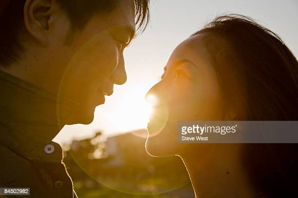 couple looking at each other close up at sunset - 向かい合わせ ストックフォトと画像