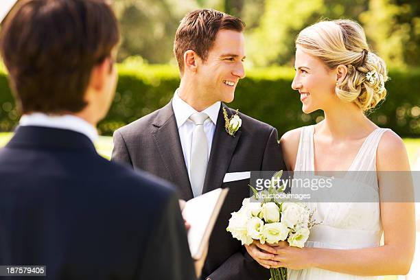 pareja mirando a otro durante boda en el jardín - sacerdote fotografías e imágenes de stock