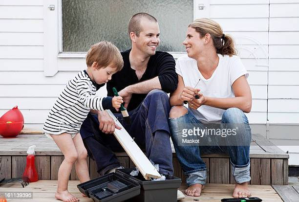 Couple looking at each other while boy painting plank