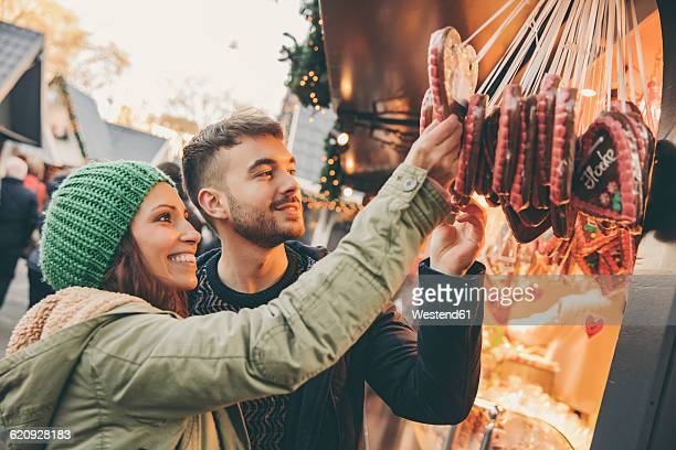 Couple looking at gingerbread hearts on the Christmas Market