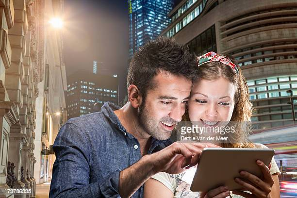 Couple looking at handheld computer device in city