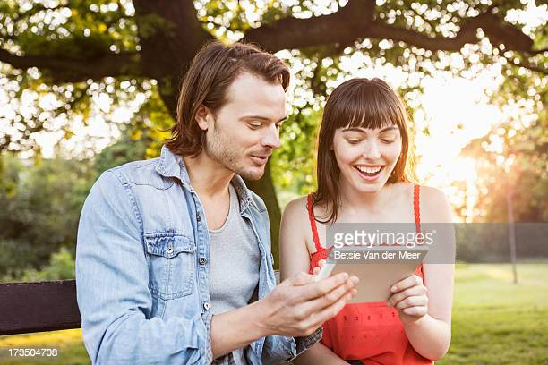 Couple looking at handhold computer device.