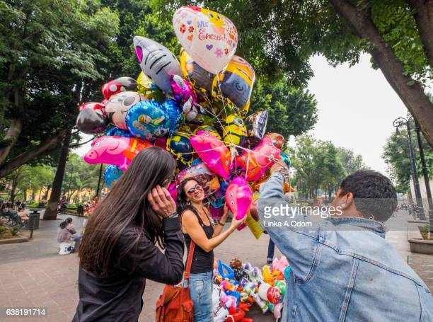 Couple looking at Helium Balloons in park