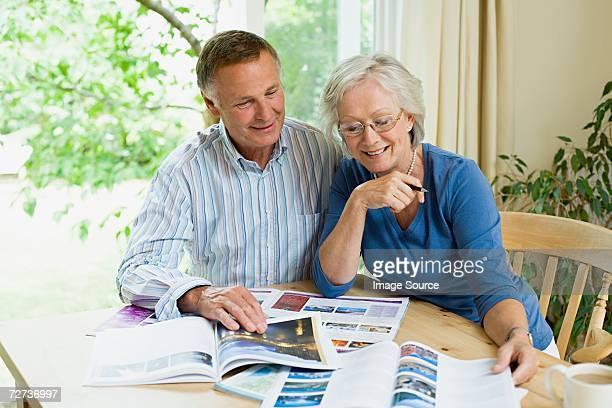 Couple à la recherche dans des brochures pour les fêtes de fin d'année