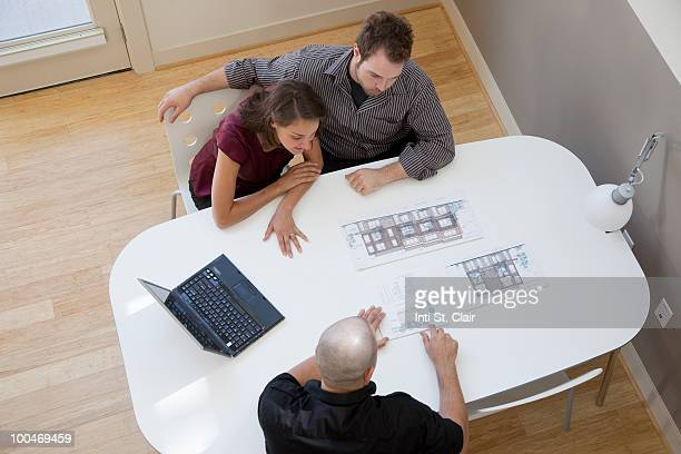 Couple looking at housing plans with developer